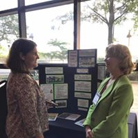 Agent June Puett discussing financial education topics with a client at a community education event.