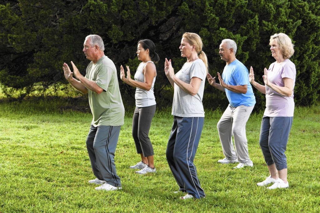 Tai Chi Class taking place outside in a park.