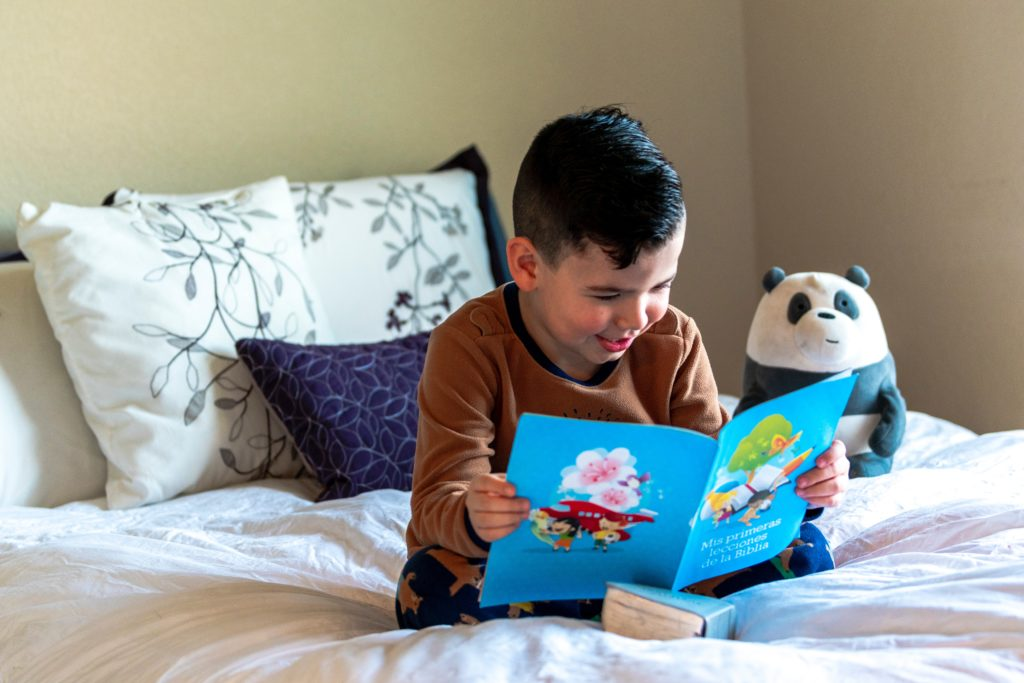 boy reading a book on a bed. Click on this image to find out more about Hamilton County 4-H programs for homeschoolers