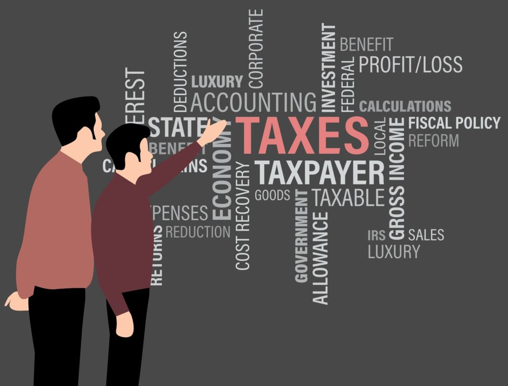 Cartoon rendering of two men discussing tax-related topics represented by financial/accounting terms displayed on a wall.