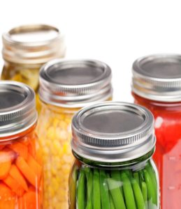 Picture of glass canning jars with canned carrots, green beans, corn and tomatoes.